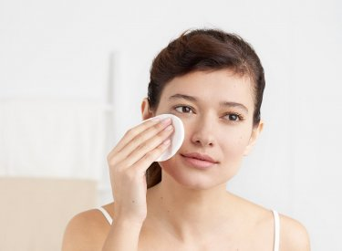 Bioderma - woman cleansing her face